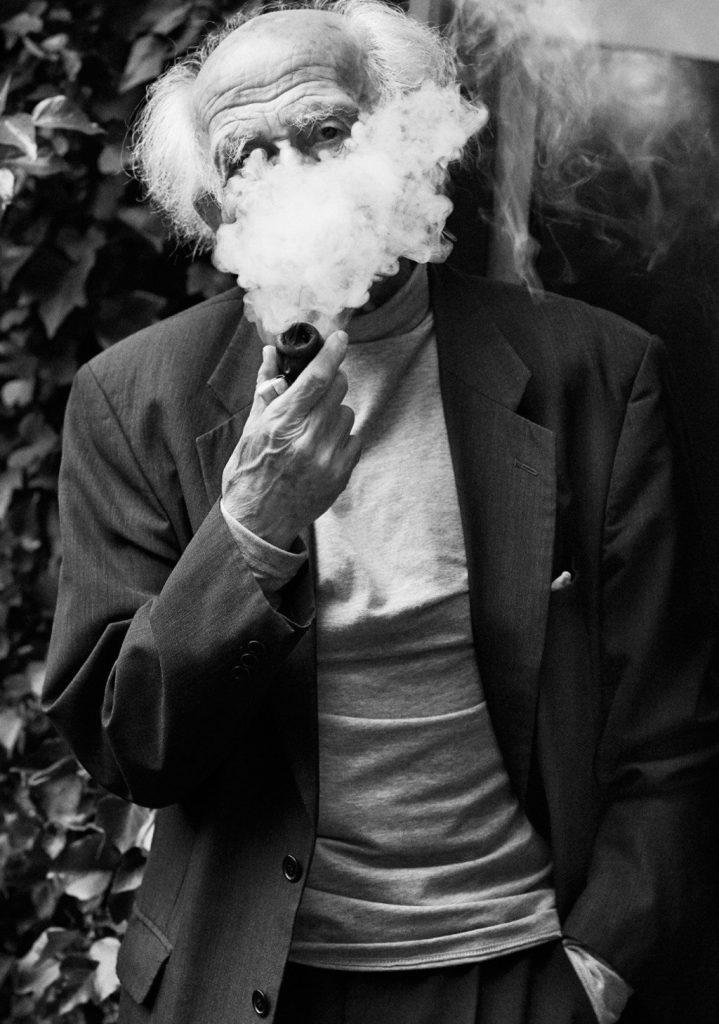 Zygmund Bauman parcialmente oculto tras el humo de su pipa - John Bolsom
